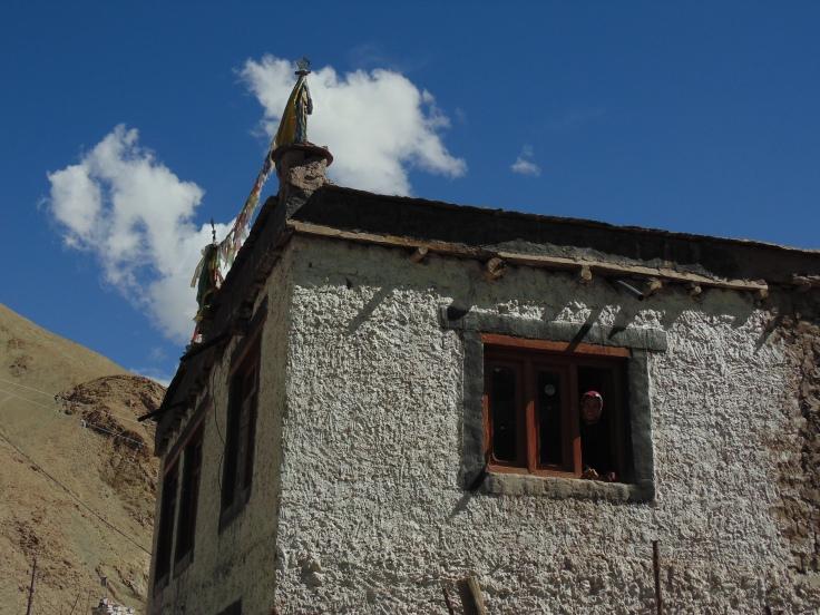 woman peeps out of mud house Miru